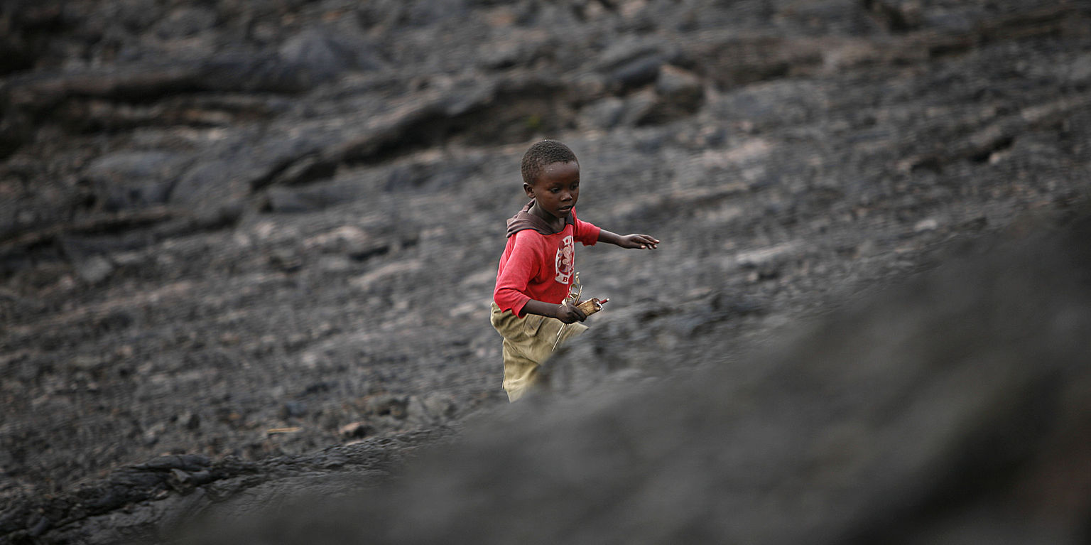 Child walking on lava from the last Nyiragongo eruption in 2002